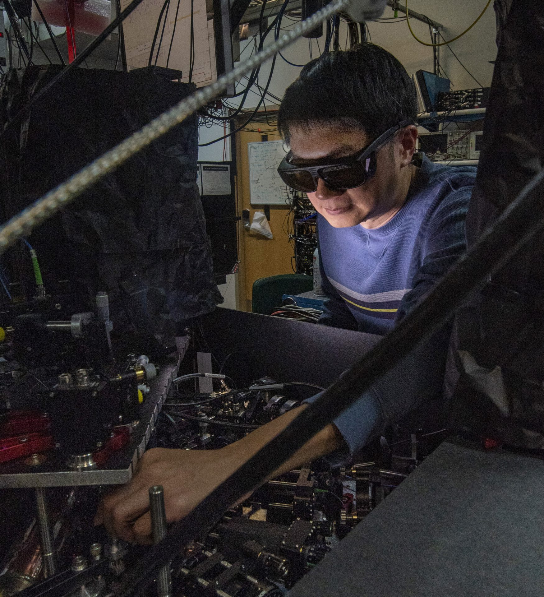 NIST physicist James Chin-wen Chou adjusts one of the laser beams used to manipulate an atom and a molecule in experiments that could help build hybrid quantum information systems. Credit: Burrus/NIST